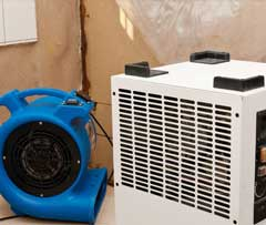 An air dryer and a fan in a corner for cleaning up from a flood
