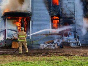 a single fireman fires his hose towarda a burning house